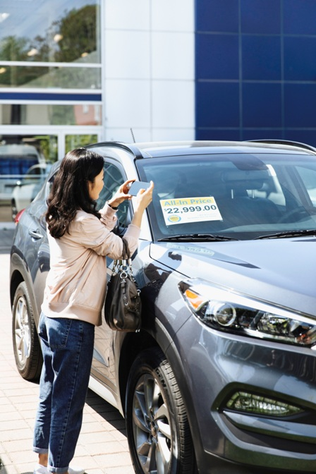 girl taking picture of car advertisement
